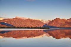 在山湖的秋天黎明 在雪的山 kolyma 库存照片