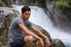 在山瀑布附近的英俊的年轻人在岩石 图库摄影
