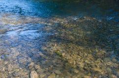 在山的一条小河沿岩石和一风雨如磐的wat流动 免版税库存照片