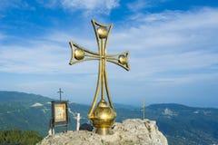 在山的上面的一个金黄十字架 免版税库存照片