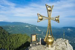 在山的上面的一个金黄十字架 库存图片
