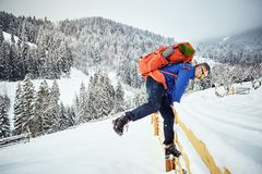 在山的上面的冬天攀登与背包的 免版税库存图片