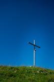 在山的上面的耶稣受难象在草甸中间的 免版税库存图片