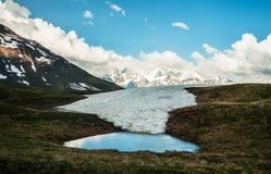 在山的上面,在多雪的山脉的看法的水池。 免版税图库摄影