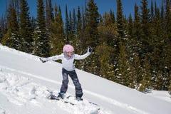 在山的下来十几岁的女孩雪板运动多雪的小山 库存图片