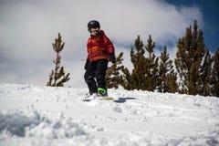 在山的下来十几岁的男孩雪板运动陡峭的多雪的小山 库存图片