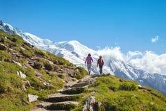 在山的两个人步行 免版税库存照片