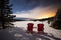 在山的两把红色椅子观看一个看法到冻湖在惊人的夜空下用星、移动的云彩和前条太阳射线,两j 库存照片