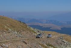 在山的两辆越野汽车 免版税库存照片