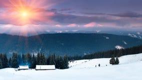 在山的五颜六色的冬天日出 发光由阳光的意想不到的早晨 多雪的森林和老木小屋客舱的看法 免版税库存图片