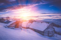 在山的五颜六色的冬天日出 发光由阳光的意想不到的早晨 多雪的森林和老木小屋客舱的看法 库存照片