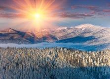 在山的五颜六色的冬天日出 雾和雪上面的看法 免版税库存照片