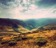 在山的五颜六色的秋天风景 减速火箭的样式 免版税库存照片