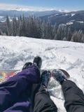 在山的休闲假期在滑雪报告 夫妇男孩和女孩的腿在美丽的雪前面 库存图片