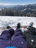 在山的休闲假期在滑雪报告 夫妇男孩和女孩的腿在美丽的雪前面 免版税库存图片