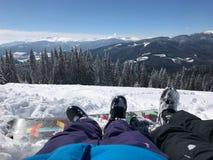 在山的休闲假期在滑雪报告 夫妇男孩和女孩的腿在美丽的雪前面 库存照片