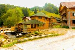 在山的假日村庄在水车旁边 库存图片