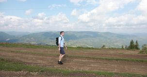 在山的偏僻的步行 英俊的年轻人沿与一个背包的小山走在他的肩膀并且看  影视素材