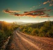在山的土路在日落剧烈的天空背景 库存图片