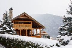 在山的圣诞节木豪宅在降雪冬日 在滑雪场的舒适瑞士山中的牧人小屋在杉木森林村庄附近  库存图片