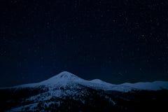 在山的多雪的山峰的上满天星斗的天空 库存图片