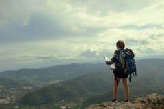 在山的妇女立场与旅行和冒险概念 免版税库存照片