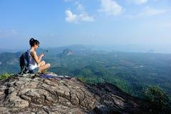 在山的妇女远足者用途数字式片剂 免版税库存照片