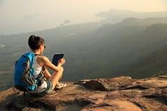 在山的妇女远足者用途数字式片剂 免版税库存图片
