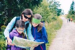 在山的家庭在上升期间 有女儿的妈妈在山的一次旅行的 学习地图-山道路  免版税库存照片