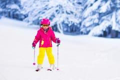 在山的小女孩滑雪 免版税库存图片