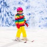 在山的小女孩滑雪 库存照片