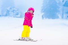 在山的小孩滑雪在冬天 库存照片