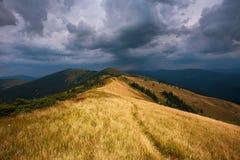在山的小山在剧烈的天空暴风云背景  库存照片