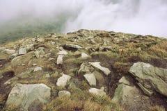 在山的岩石在雾背景  免版税库存照片