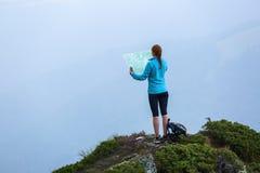 在山的峰顶有地图和指南针的touris女孩搜寻方式作梦 在雾的天际 免版税库存照片