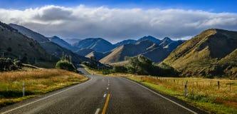 在山的平直的空的路,新西兰 免版税库存照片