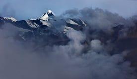 在山的强的雾:黑暗的云彩包围黑褐色山,在顶部谎言白色冰川,西藏 库存照片