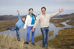 在山的愉快的家庭与湖 库存照片