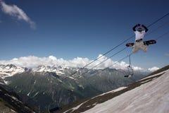 在山的挡雪板飞行 免版税库存照片