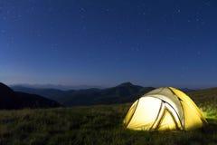 在山的旅游远足者帐篷在与星的晚上在天空 库存图片