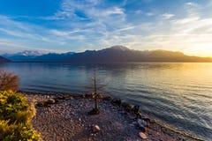 在山的日落与湖和海岸线 库存照片