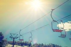 去在山的日落和滑雪电缆车 免版税图库摄影