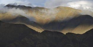 在山的日落:土坎小山波浪线在透明白色云彩中丢失 免版税库存图片