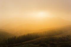 在山的有雾的日落 免版税库存图片