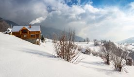在山的木舒适瑞士山中的牧人小屋与从烟囱的烟 免版税库存照片
