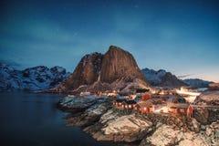在山的极光borealis与Hamnoy的渔村 免版税库存照片