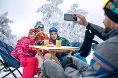 在山的滑雪期间家庭采取小休 库存图片