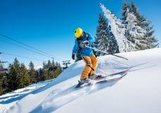 在山的滑雪者骑马在一个晴朗的冬日 库存照片