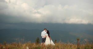 在山的爱 男人和妇女互相举行站立在小山和观看的雨的手很远在 股票视频