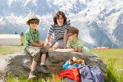 在山的父亲和两个儿子休息 免版税库存图片
